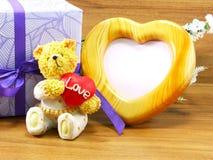 L'ours brun de nounours et le coeur rouge forment avec le cadre de photo de forme de coeur Images stock
