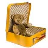 L'ours de nounours antique se reposant dans une valise jaune veut voyager Image stock