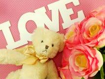L'ours de nounours avec le mot d'amour et les roses artificielles fleurissent Image libre de droits