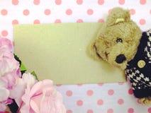 L'ours de nounours avec le mot d'amour et les roses artificielles fleurissent Photographie stock libre de droits