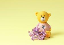 L'ours de nounours avec un coeur et un lilas fleurit sur un fond jaune Image stock