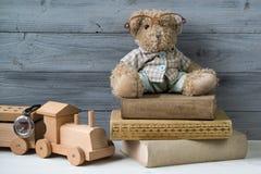 L'ours de nounours en verres sur les vieux livres et le jouet en bois s'exercent Images libres de droits