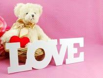 L'ours de nounours mignon avec le mot d'amour et les roses artificielles fleurissent Photos libres de droits