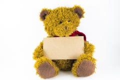 L'ours de nounours repose et tient un signe jaune vide Photographie stock