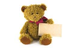 L'ours de nounours repose et tient un signe jaune vide Photo stock