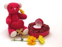 L'ours de nounours rouge reposent la prise le coeur rouge par le côté avec la boîte rouge en forme de coeur, en forme de coeur ro Image stock