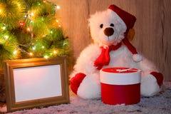 L'ours de nouvelle année, de Noël se reposant sous un arbre de sapin avec des maquettes d'un cadre en bois pour une photo ou le t photographie stock libre de droits