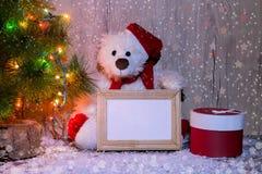 L'ours de nouvelle année, de Noël se reposant sous un arbre de sapin avec des maquettes d'un cadre en bois pour une photo ou le t images stock