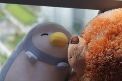 L'ours et le pingouin jouent se reposer par la fenêtre dans les ombres Photos libres de droits