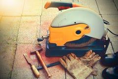 L'outil de coupe, les gants, le marteau, le burin et les chaussures ont mis dessus la brique Images libres de droits