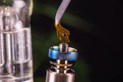 L'outil tamponnant avec le petit morceau de cannabis huilent aka l'éclat - medi photos libres de droits