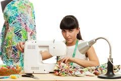 L'ouvrière couturière coud un produit sur une table Images stock