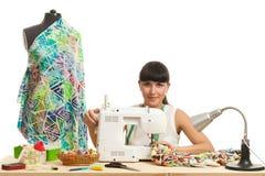 L'ouvrière couturière coud un produit sur une table Images libres de droits