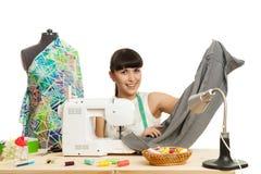 L'ouvrière couturière coud un produit sur une table Photo stock