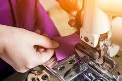 L'ouvrière couturière dans un unifrome pourpre coud le cuir véritable Images stock