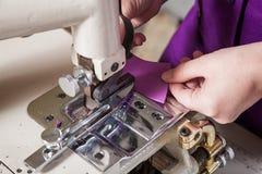 L'ouvrière couturière dans un unifrome pourpre coud le cuir véritable Photo stock
