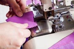 L'ouvrière couturière dans un unifrome pourpre coud le cuir véritable Image stock