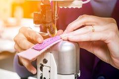 L'ouvrière couturière dans un unifrome pourpre coud le cuir véritable Images libres de droits