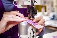 L'ouvrière couturière dans un unifrome pourpre coud le cuir véritable Photographie stock libre de droits
