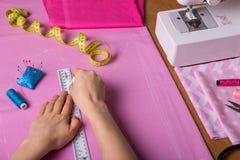 L'ouvrière couturière de mains a coupé le tissu sur le bureau, près des accessoires et de la machine de couture Photographie stock libre de droits