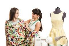 L'ouvrière couturière essaye le tissu sur la fille Images stock