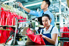 Surveillant d'ouvrière couturière et de décalage dans l'usine de textile Photo stock
