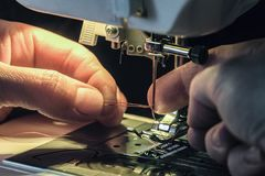 L'ouvrière couturière passe le fil dans le threader d'aiguille de la machine à coudre Images stock
