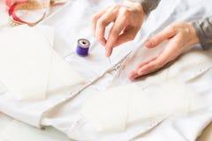 L'ouvrière couturière pique la tirette à un matériel blanc avec le fil pourpre Photos libres de droits