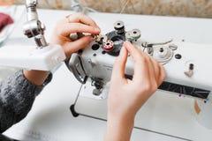 L'ouvrière couturière remplacent la bobine dans la machine à coudre Photographie stock libre de droits
