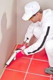 L'ouvrier étend la puate d'étanchéité de canon de silicones Photographie stock