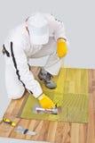L'ouvrier applique l'adhésif de tuile sur l'étage en bois Image libre de droits