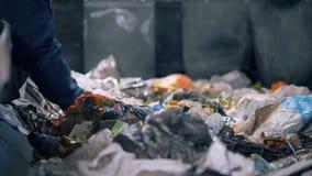 L'ouvrier assortit des déchets sur une ligne, fin  Un travailleur assortit le papier sur une ligne mobile complètement des déchet banque de vidéos