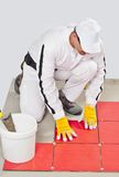 L'ouvrier avec l'adhésif de position appliquent les tuiles rouges Photo stock