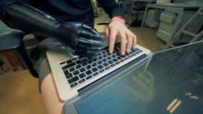 L'ouvrier avec une main robotique dactylographie sur un ordinateur portable sur ses genoux 4K clips vidéos