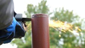 L'ouvrier coupe une pipe en métal banque de vidéos
