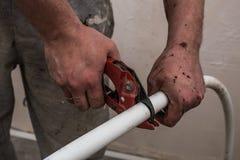 L'ouvrier de plombier coupe instamment le tuyau blanc de mains sales au repa photographie stock libre de droits
