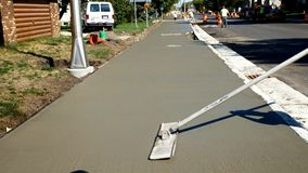 L'ouvrier finit et lisse la surface en béton sur le nouveau trottoir clips vidéos