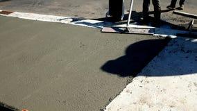 L'ouvrier finit et lisse la surface en béton sur le nouveau trottoir banque de vidéos
