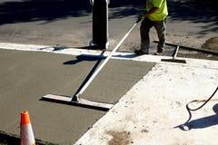 L'ouvrier finit et lisse la surface en béton sur le nouveau trottoir photographie stock