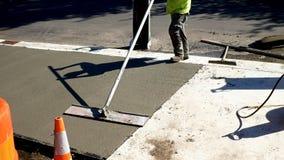 L'ouvrier finit et lisse la surface en béton sur le nouveau trottoir images libres de droits
