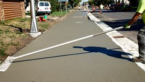 L'ouvrier finit et lisse la surface en béton sur le nouveau trottoir image stock