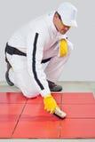 L'ouvrier nettoie des joints avec le balai en bois Photo stock