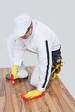 L'ouvrier nettoie l'étage en bois Photographie stock