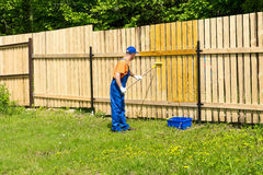 L'ouvrier peint la barrière en bois avec un rouleau de peinture Photos libres de droits