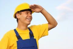 L'ouvrier regardant vers l'avant, couvrant observe du soleil Photo libre de droits