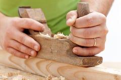 L'ouvrier remet le plan rapproché - bois de rabotage Image libre de droits