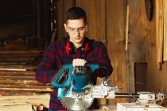 L'ouvrier s'est habillé dans la chemise à carreaux fonctionnant avec la scie circulaire à la scierie photographie stock libre de droits