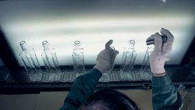 L'ouvrier vérifie la qualité, vue supérieure Un travailleur utilise un outil pour examiner la qualité de ` de bouteilles à une us clips vidéos