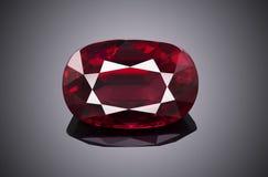 L'ovale de scintillement transparent rouge de luxe de forme de pierre gemme a coupé le rubis d'isolement sur le fond gris image libre de droits