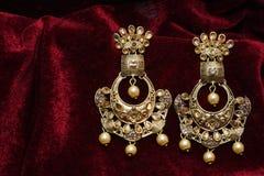 L'or a plaqué des bijoux - macro image boucles d'oreille d'or de fantaisie de concepteur de longues photos libres de droits